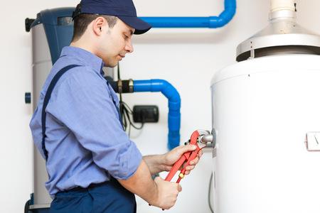 Plumber repairing an hot-water heater Archivio Fotografico