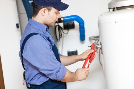 maintenance fitter: Plumber repairing an hot-water heater Stock Photo
