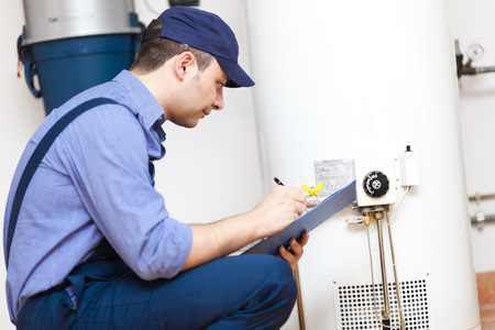 Technician repairing an hot-water heater Stock Photo