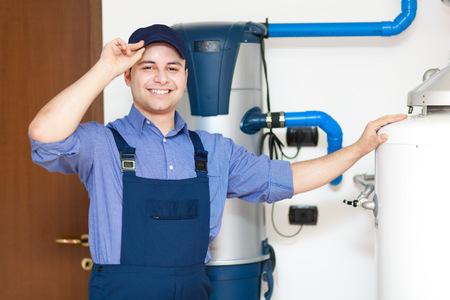 upkeep: Smiling technician repairing an hot-water heater Stock Photo