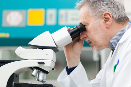 analytical chemistry: Man using a microscope in a laboratory Stock Photo