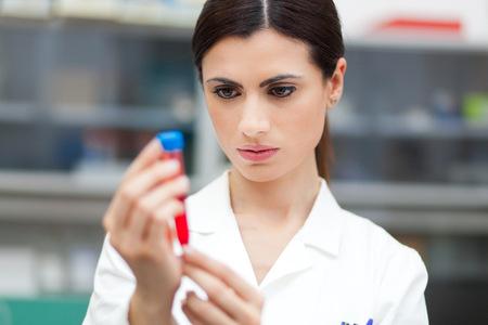 in vitro: Mujeres científico mirando un tubo de ensayo