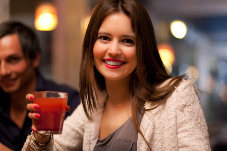 Woman drinking a cocktail in a pub photo