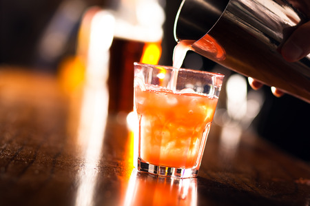 Bartender serving a cocktail from a shaker