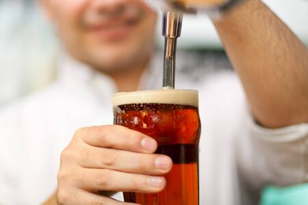 Detail of a bartender drawing a beer Stock Photo