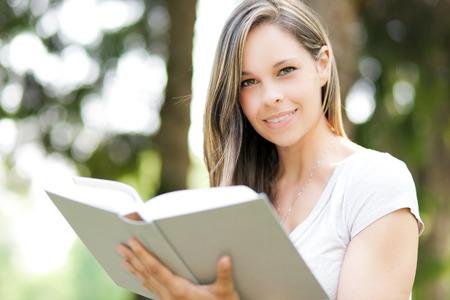 mujer leyendo libro: Muchacha hermosa que lee un libro en el parque Foto de archivo