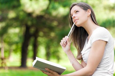 persona escribiendo: Muchacha en el parque escribe en su diario personal