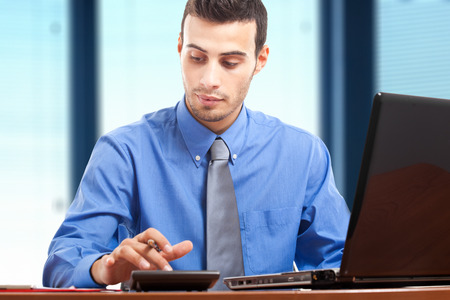 Young businessman accounting at his desk photo