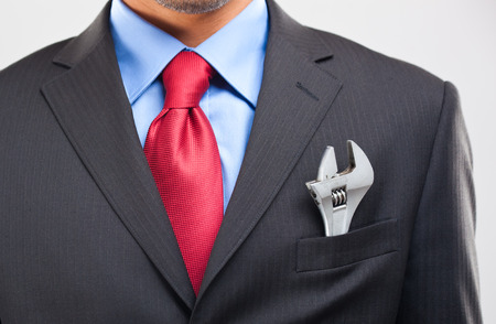 Business man keeping an adjustable wrench in his pocket