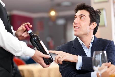 Customer choosing a wine bottle in a restaurant photo