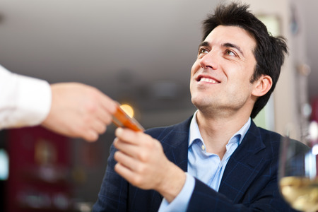 satisfied people: Man paying dinner in a restaurant