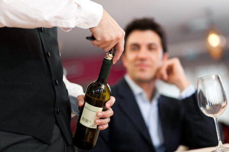 christmas catering: Waiter uncorking a wine bottle in front of a customer