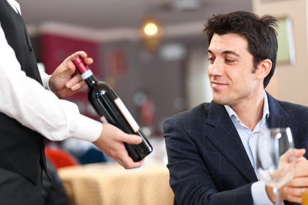 レストランでワインのボトルを選択するお客様
