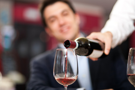 waiter: Waiter pouring wine to a customer Stock Photo