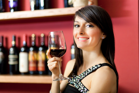 Woman tasting a glass of red wine photo