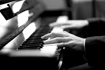 Close-up van een muzikant spelen van een piano toetsenbord. Zwart-wit beeld
