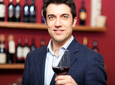 Handsome man holding a glass of wine photo