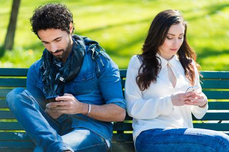 single woman: Pareja sin hablar el uno al otro a escribir en los teléfonos móviles