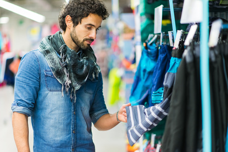 man searching: Handsome young man searching for clothes in a shop Stock Photo