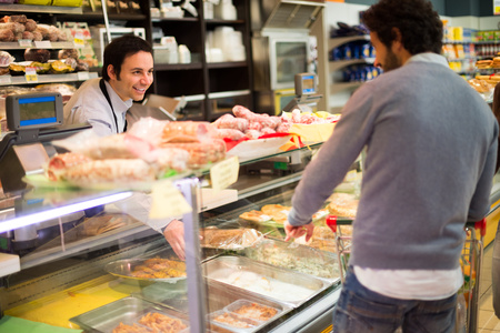butcher: Shopkeeper serving a customer in a grocery store