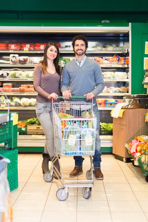 Smiling couple grocery shopping in a supermarket Zdjęcie Seryjne