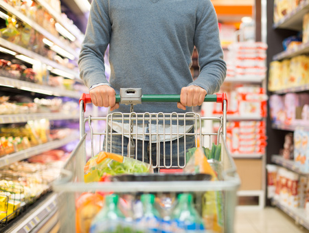 grocery shopping cart: Detail of a person shopping in a supermarket Stock Photo