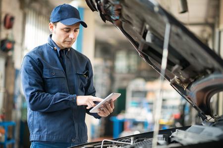 mechanic: Retrato de un mecánico con una tableta en su garaje Foto de archivo