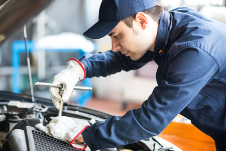 Portrait of an auto mechanic at work on a car in his garage 스톡 콘텐츠