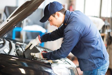 Portret van een automonteur zetten olie in een auto-motor
