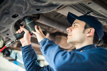 mot: Portrait of a mechanic repairing a car in his garage