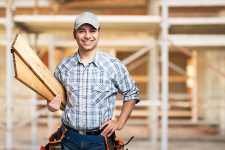 Portret van een glimlachende timmerman die houten planken in een bouwplaats