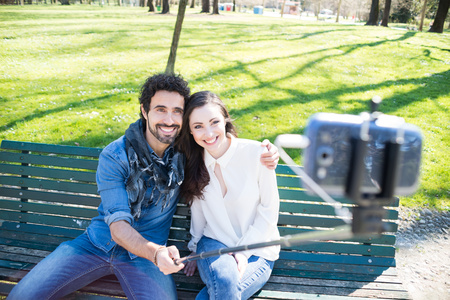 Couple using a selfie stick in a park photo