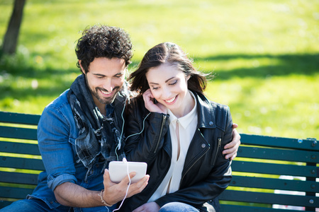 Couple listening music in a park photo