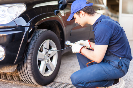 car tire: Tire specialist checking the pressure of a tire Stock Photo