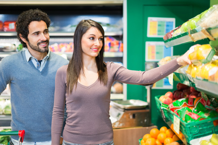 Couple grocery shopping in a supermarket photo