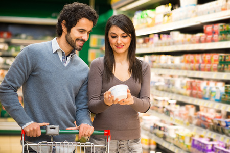 woman shopping cart: Young couple choosing food in a supermarket Stock Photo