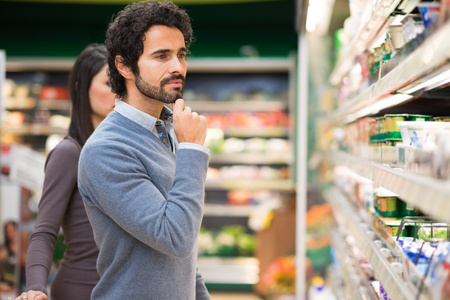 Handsome man shopping in a supermarket photo