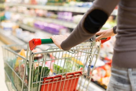 woman shopping cart: Woman grocery shopping in a supermarket Stock Photo