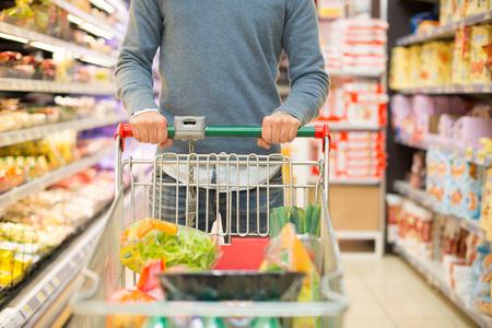 O detalhe do close-up de um homem de compras em um supermercado