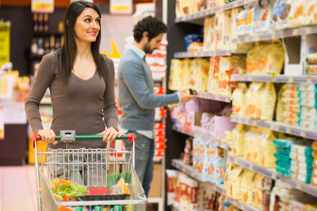 groceries shopping: Young couple shopping in a grocery store Stock Photo