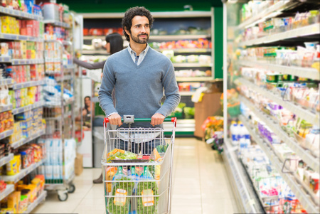 supermarkets: Handsome man shopping in a supermarket