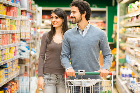 woman shopping cart: Young couple shopping in a supermarket