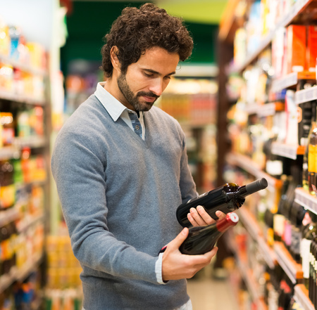 Man in a supermarket choosing a wine photo