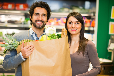 Smiling couple holding a shopping bag full of food in a supermarket photo