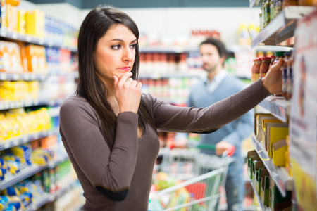 woman shopping cart: Woman shopping in a supermarket Stock Photo
