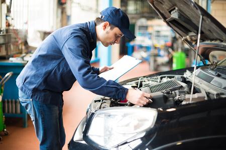 motor coche: Retrato de un mecánico en el trabajo en su garaje