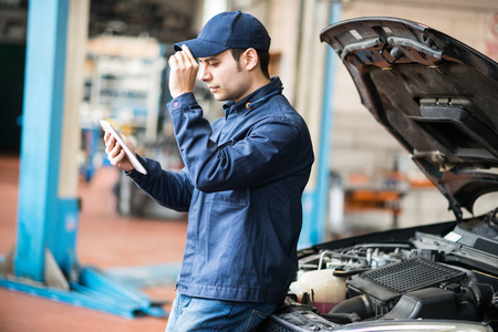 mot: Portrait of a mechanic using a tablet in his garage