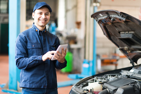 budget repair: Portrait of a mechanic using a tablet in his garage