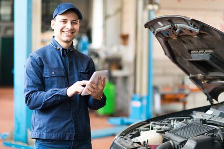 Portret van een monteur met behulp van een tablet in zijn garage