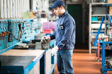 vise: Trabajador asegurar una placa de metal en un tornillo de banco